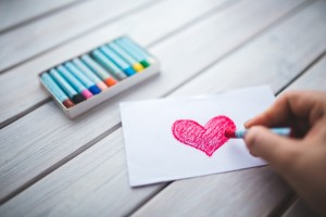 hand-with-oil-pastel-draws-the-heart