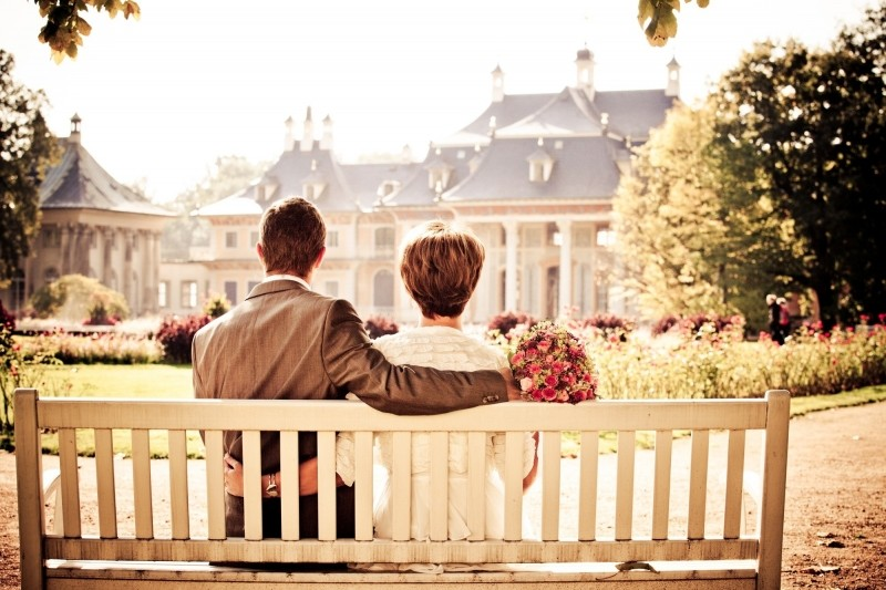 young-couple-with-wedding-bouquet-sitting-on-bench