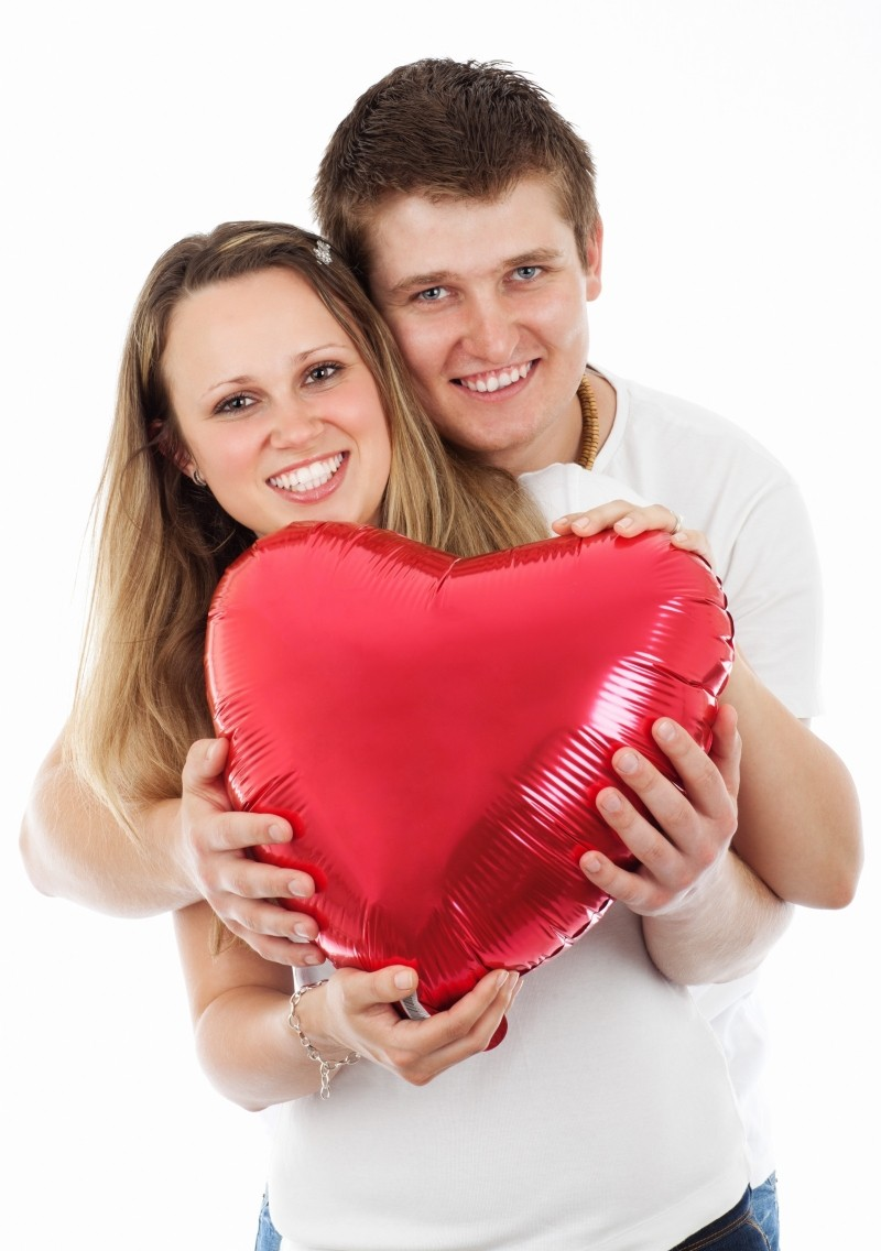 young-smiling-couple-posing-with-red-heart-on-white-background